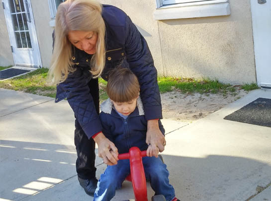 Picture of woman helping a young boy on a tricycle