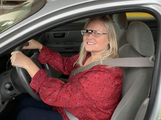 Woman driving while wearing a bioptic telescopic lense