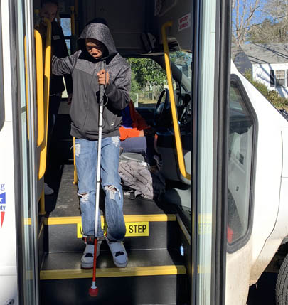 O&M Student with a long cane getting off a bus