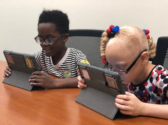 Two students learning to use iPads